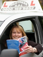 Diane Hall with her book in her driving school car